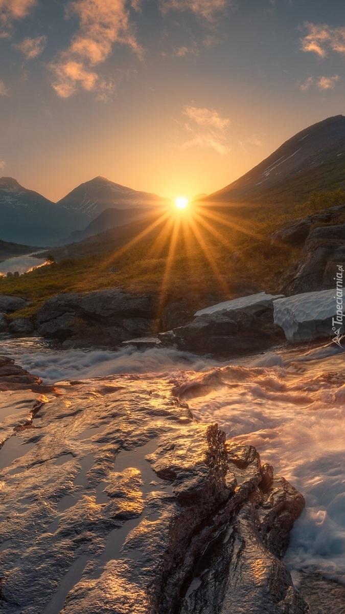 Promienie słońca nad rwącą rzeką