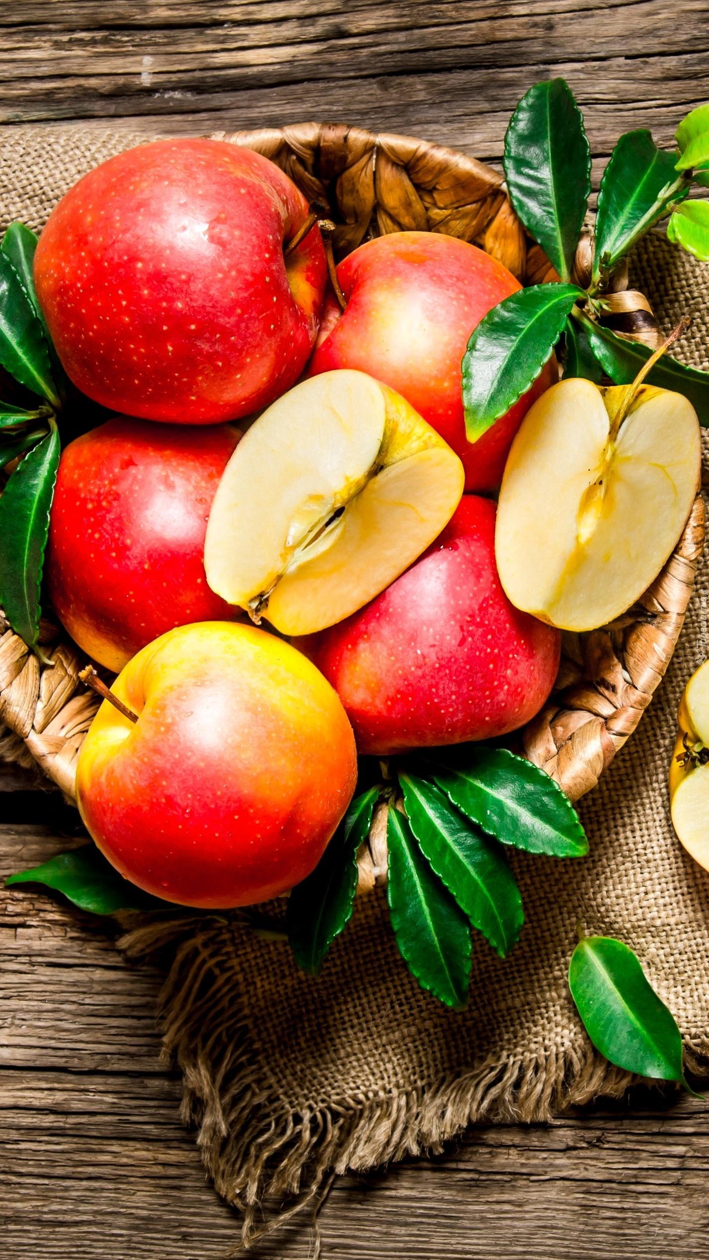 Przyozdobione listkami jabłka w koszyku