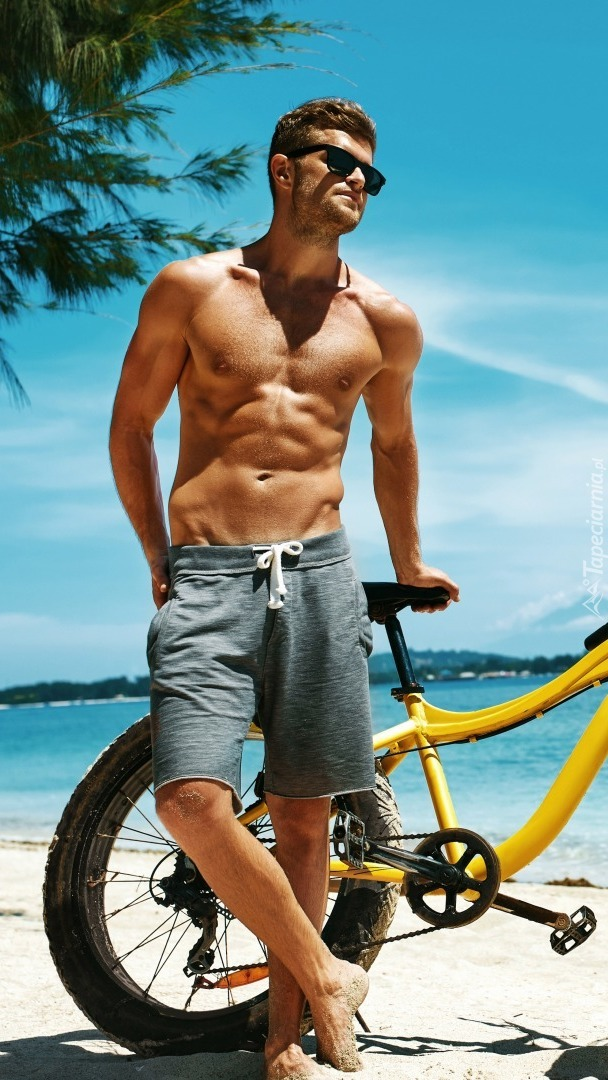Przystojniak z rowerem na plaży