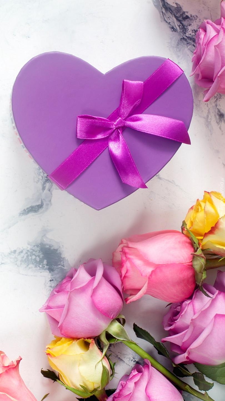 Pudełko w kształcie serca obok róż