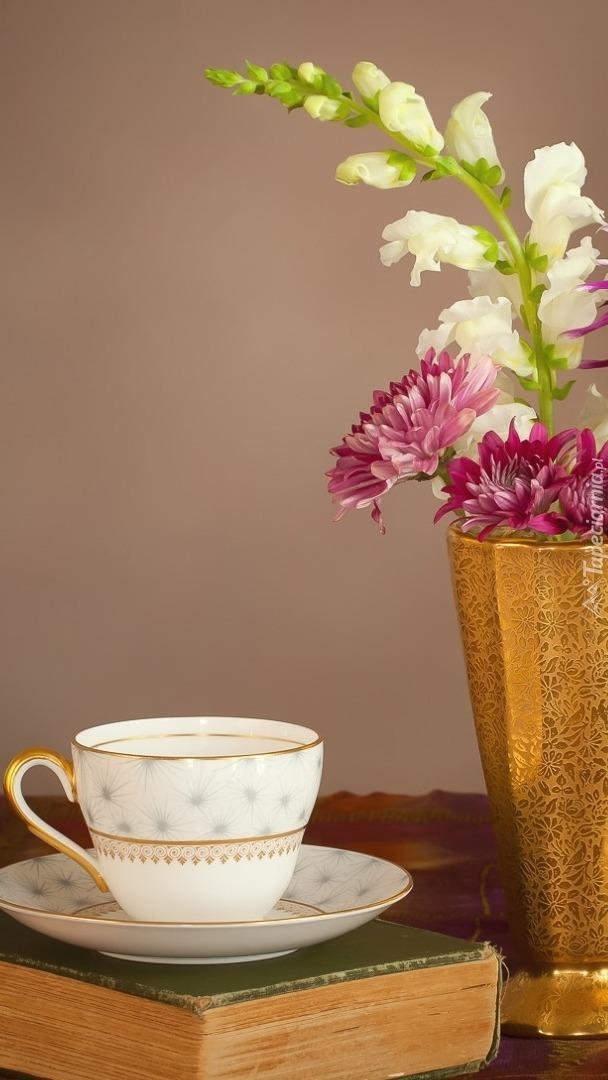 Pusta filiżanka obok wazonu z kwiatami i książka
