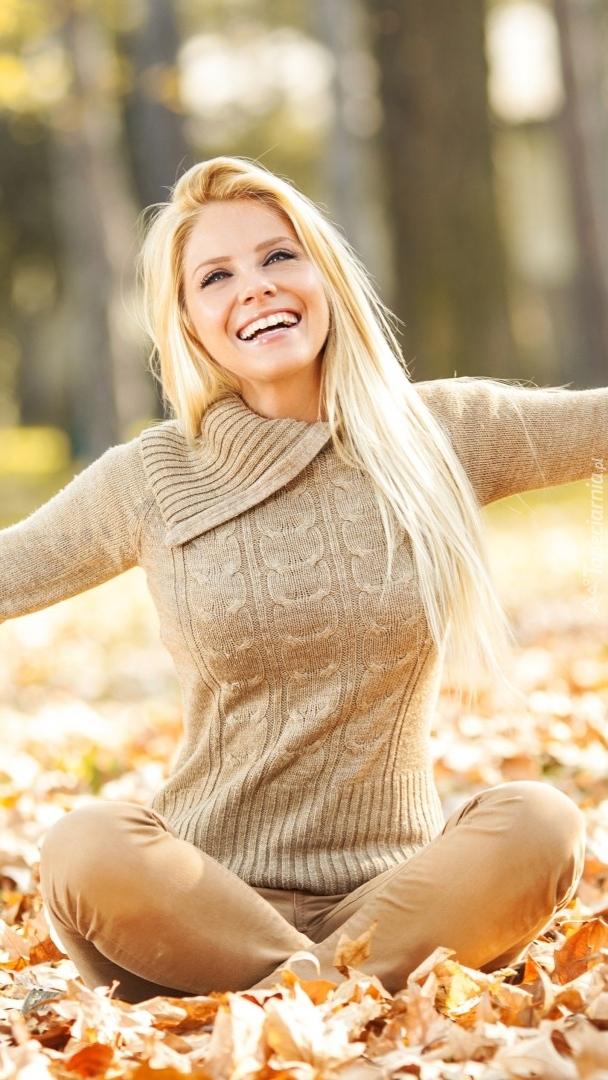 Radosna kobieta w jesiennych liściach