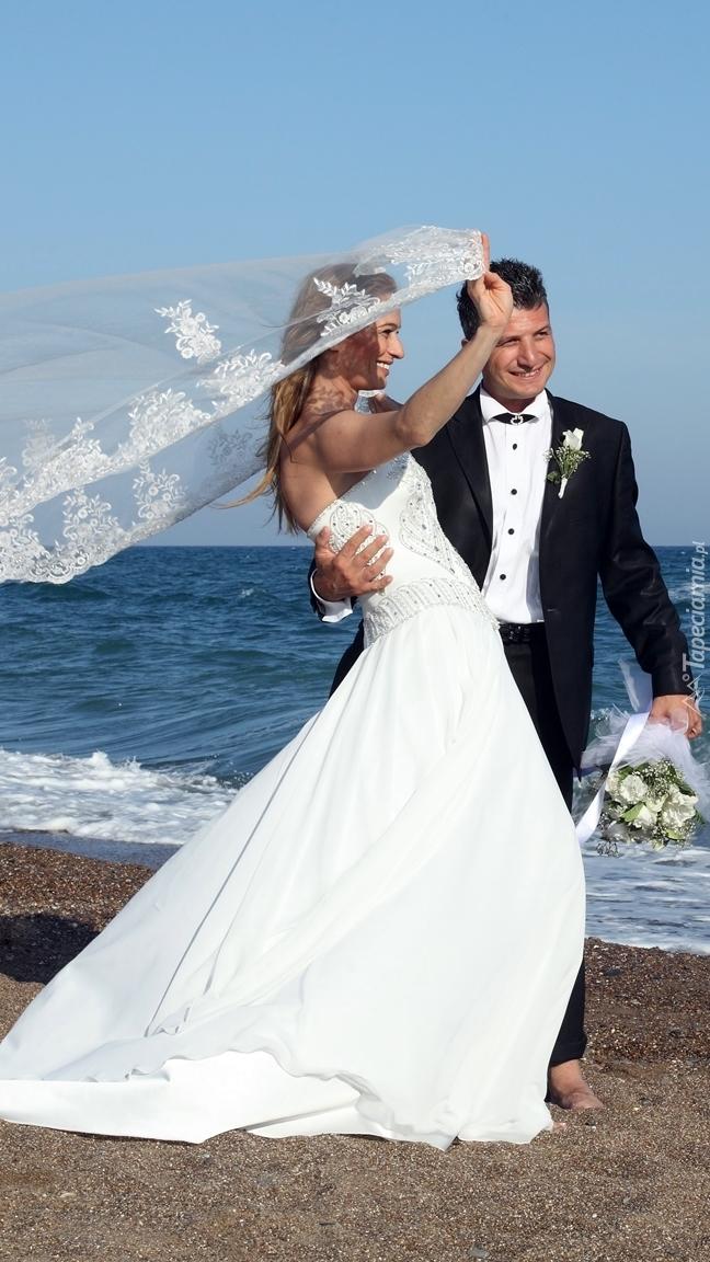Radośni nowożeńcy nad morzem