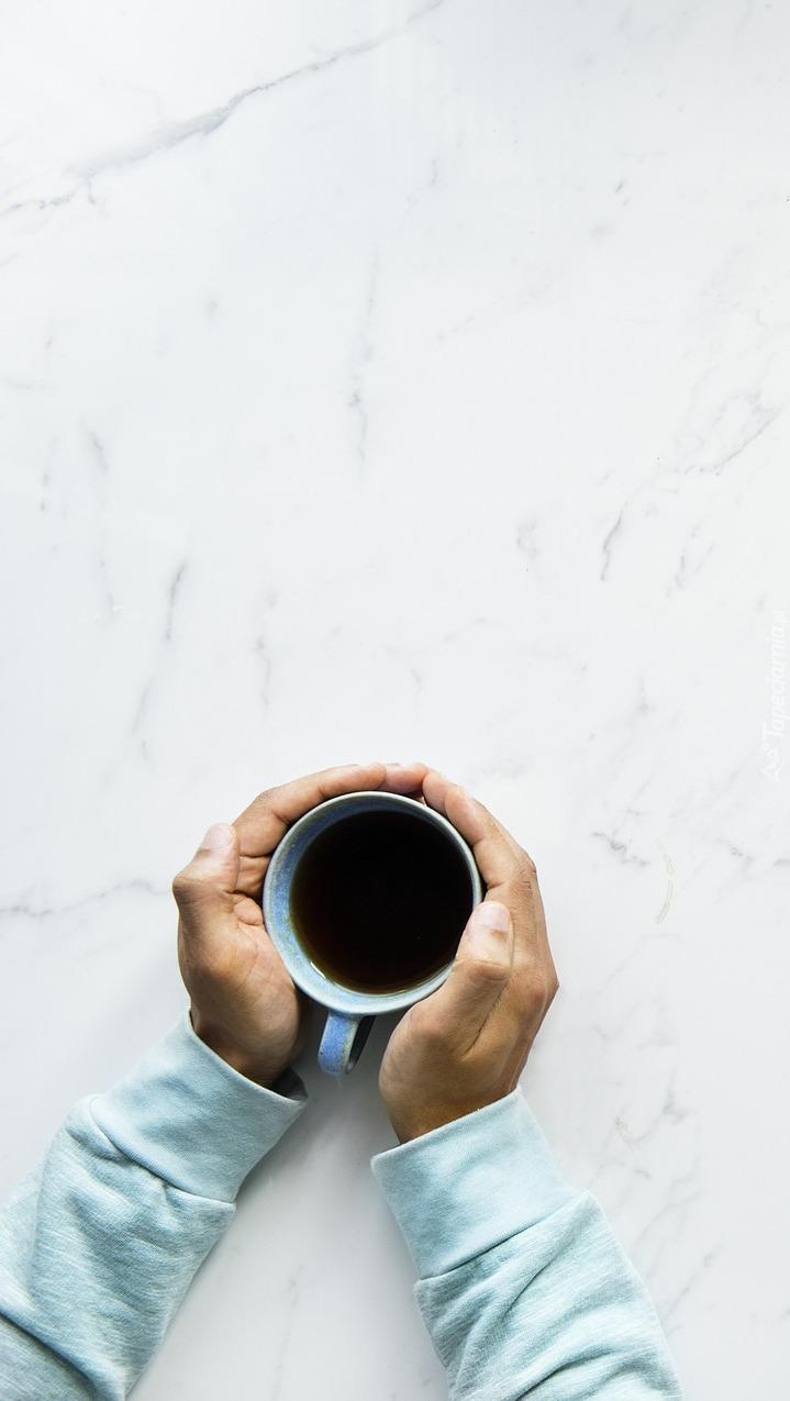 Ręce mężczyzny trzymające kubek kawy