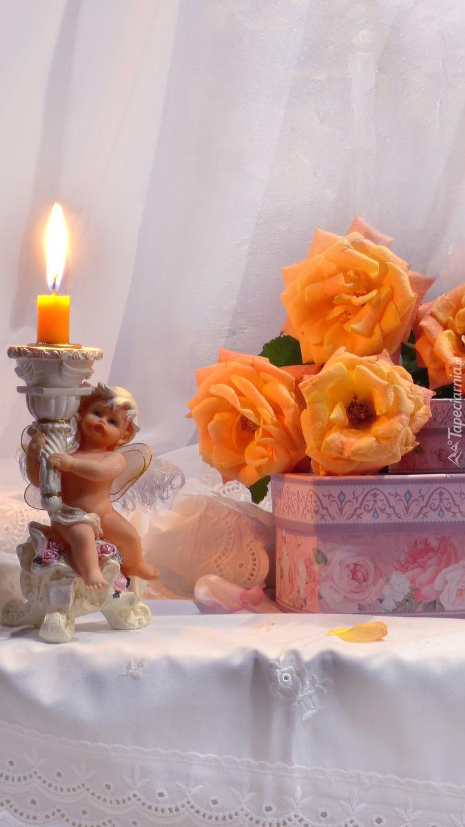 Róże na pudełkach obok świecznika z aniołkiem