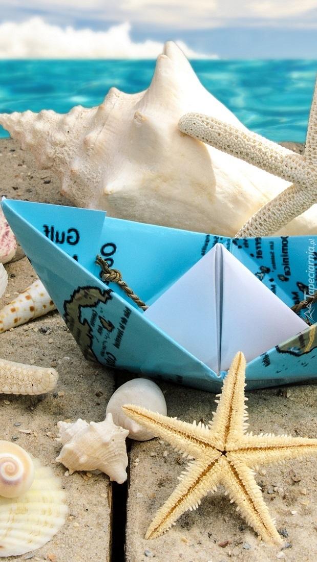 Rozgwiazdy i muszelki obok papierowego statku