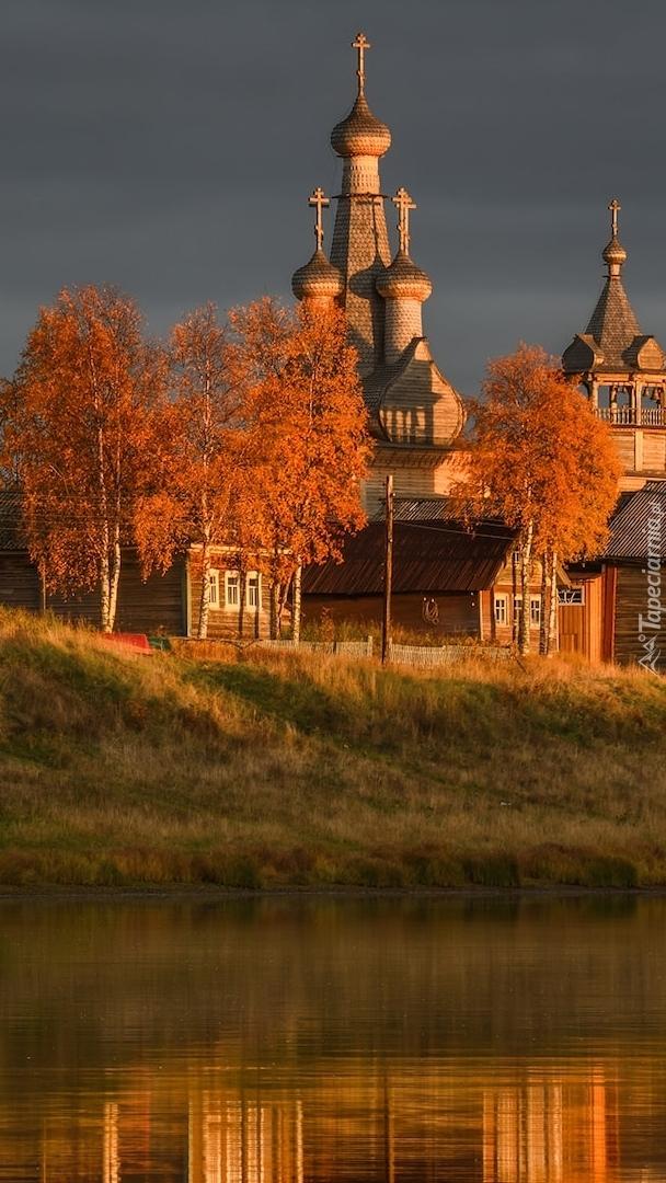 Rozświetlone słońcem jesienne drzewa i cerkiew