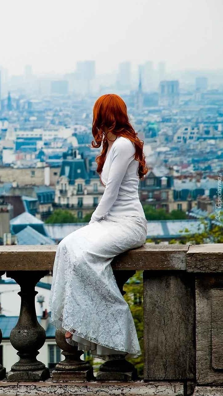Rudowłosa kobieta patrząca na miasto
