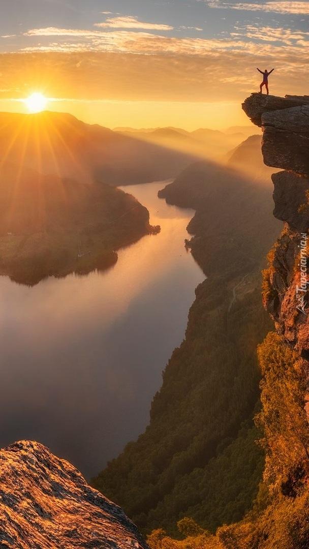 Rzeka w blasku słońca i człowiek na skale