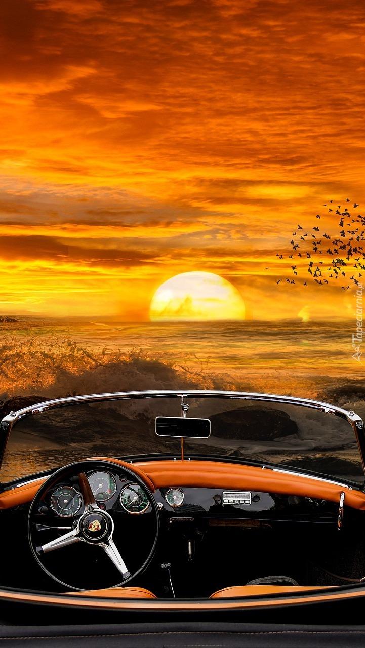 Samochód na brzegu morza w zachodzącym słońcu