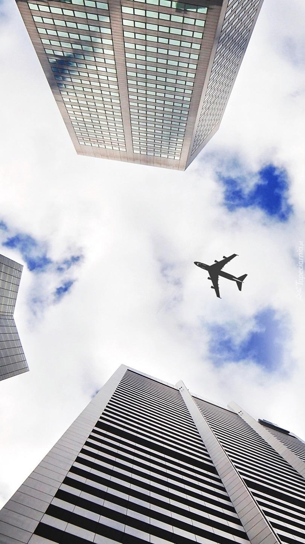 Samolot ponad drapaczami chmur