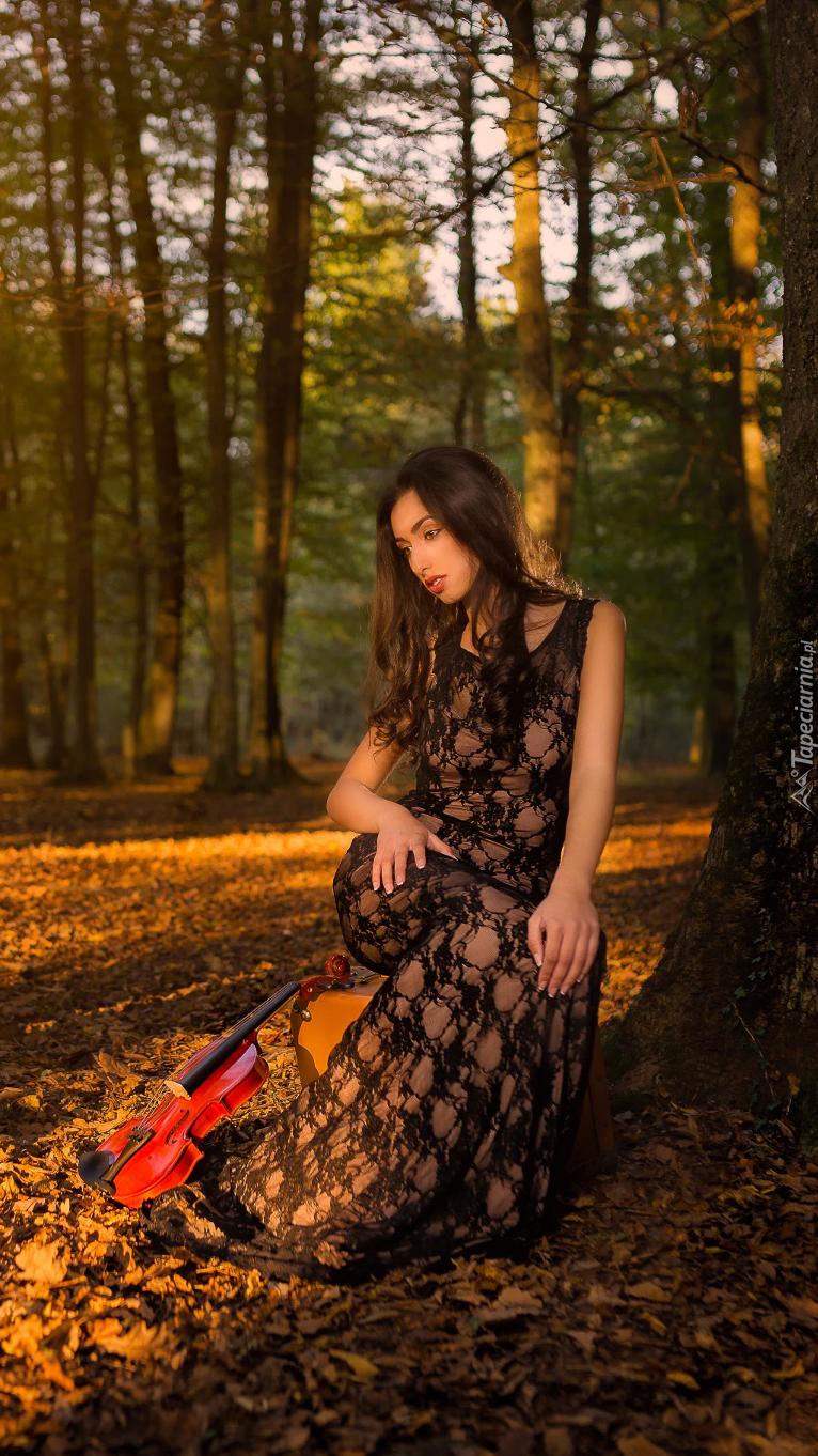 Siedząca kobieta ze skrzypcami pod drzewem