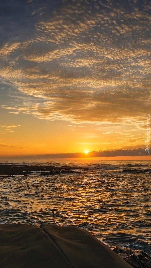 Skaliste wybrzeże morskie o zachodzie słońca
