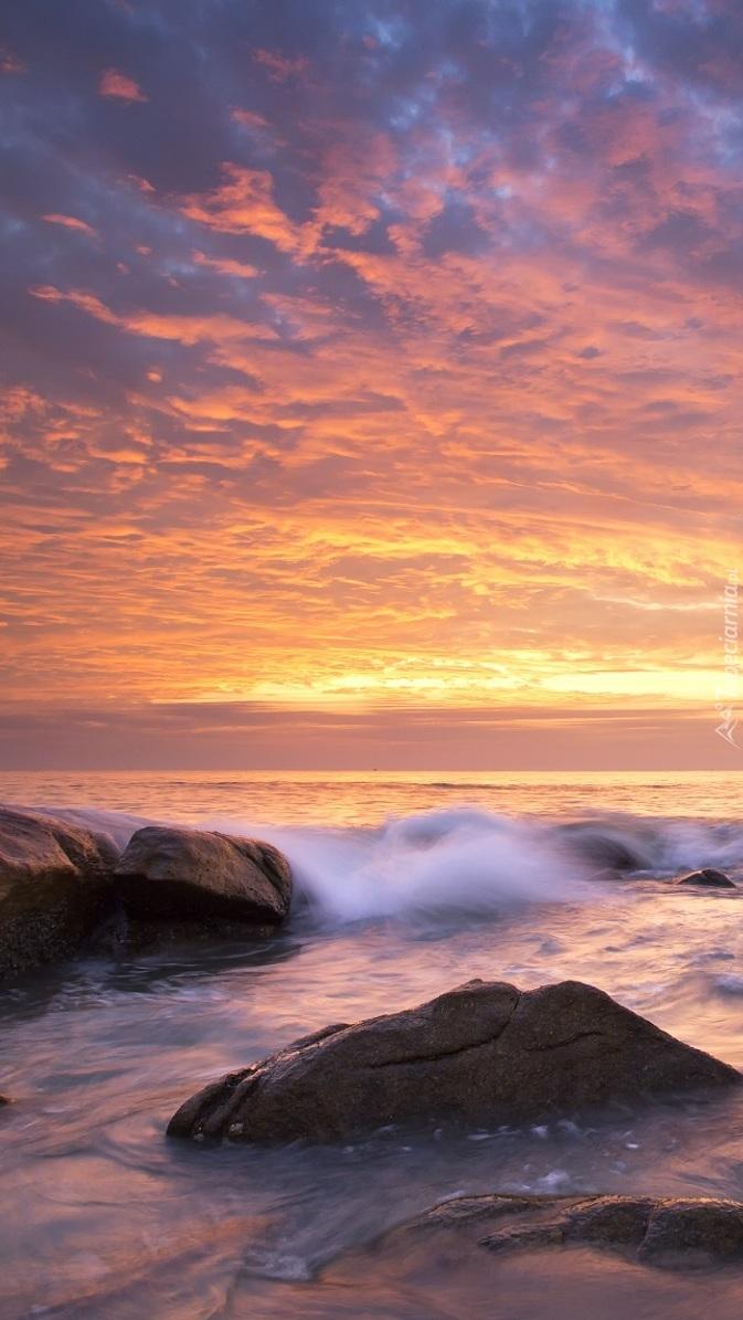 Skały na brzegu morza w zachodzącym słońcu