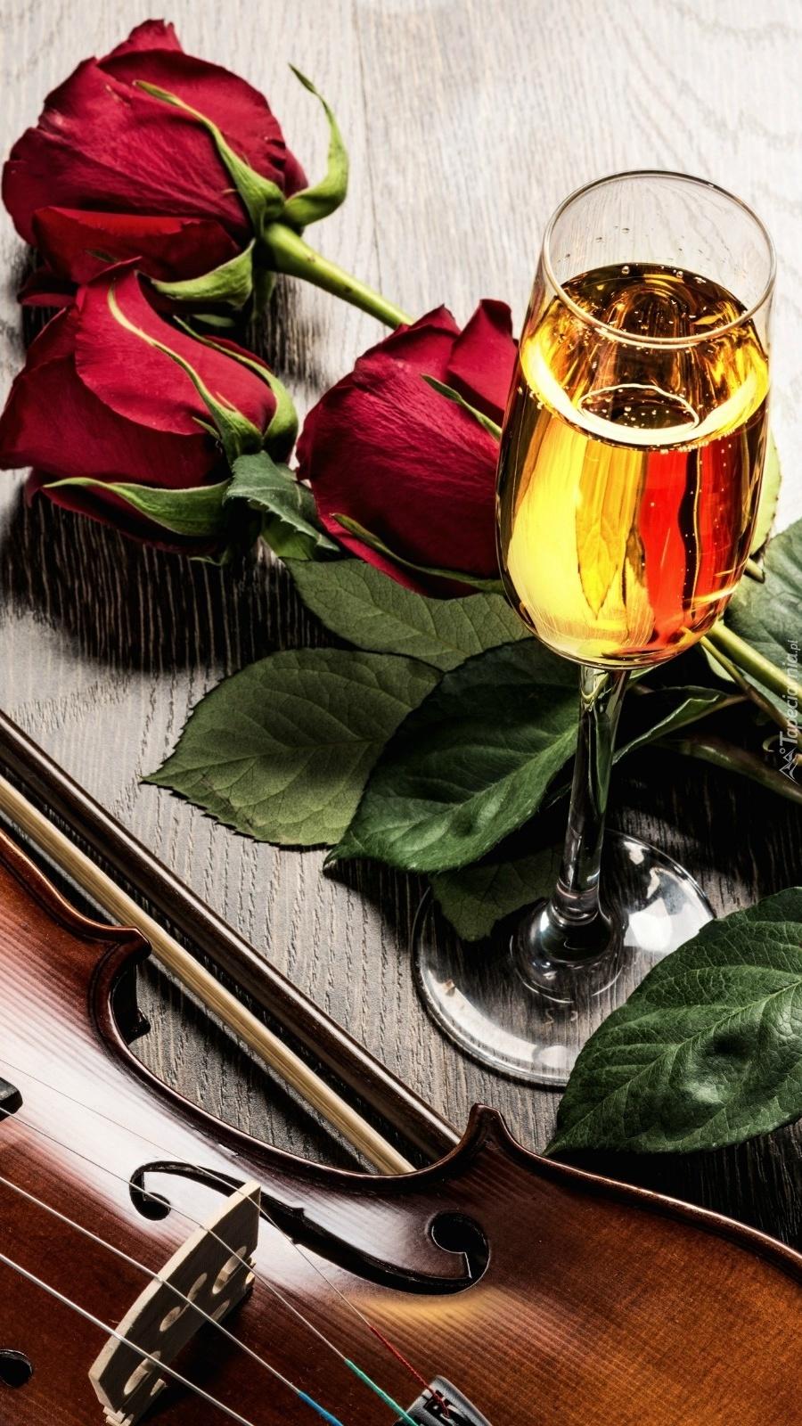 Skrzypce obok lampki wina i róż