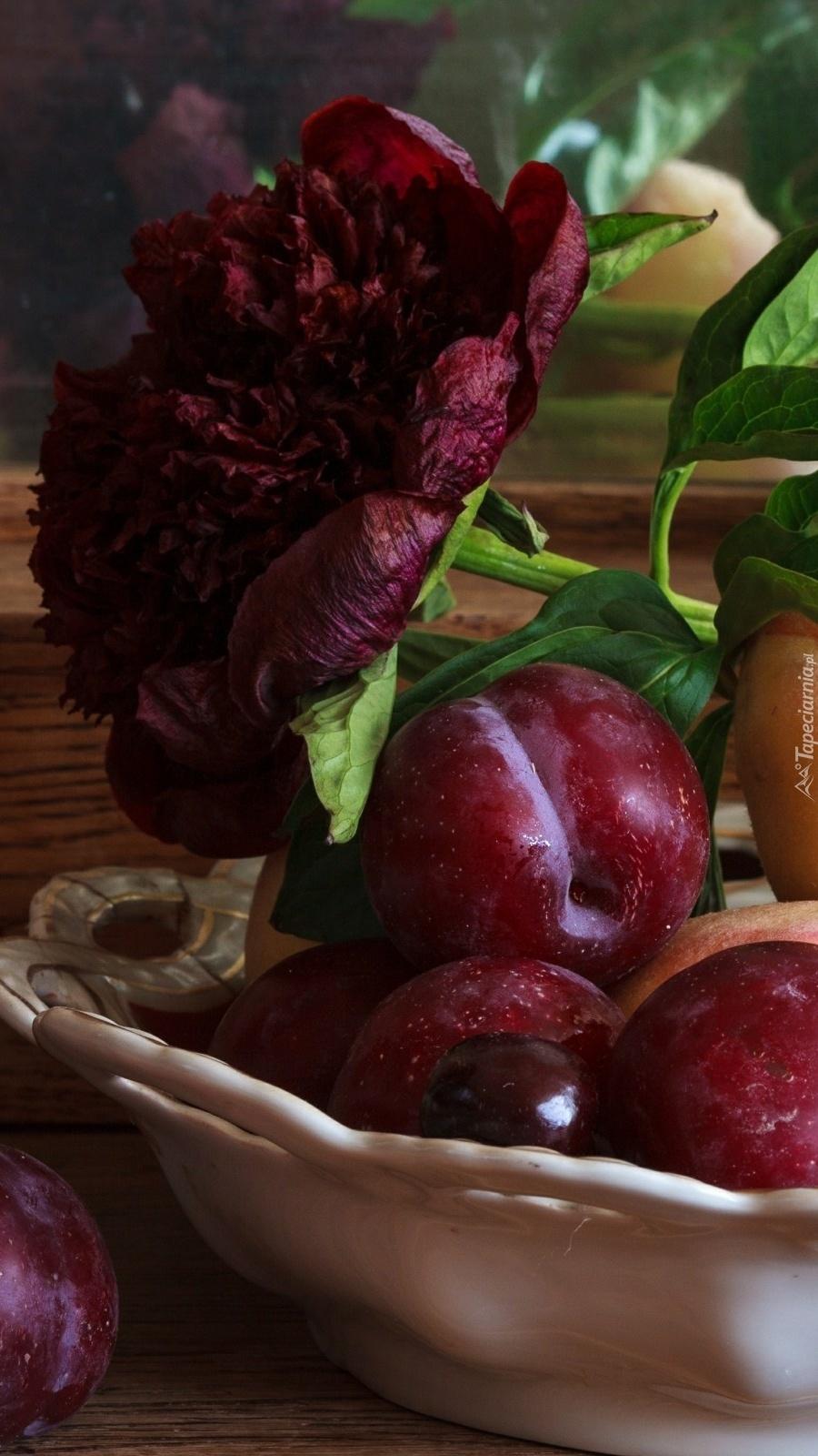 Śliwki w misce przyozdobione piwonią