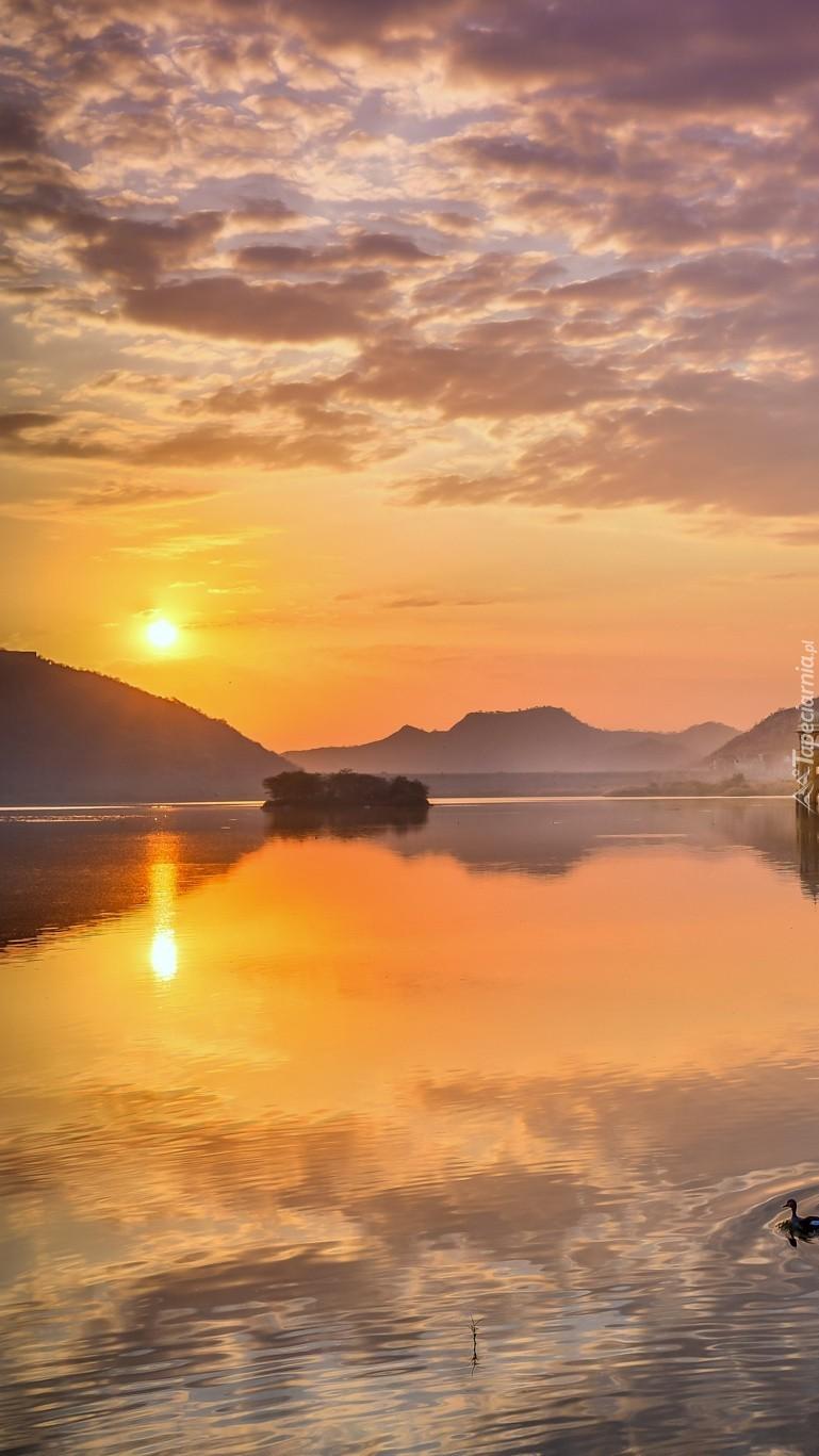Słońce zachodzi nad spokojnym jeziorem