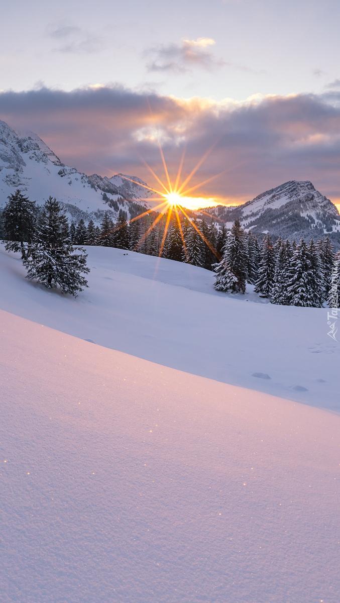 Słoneczne promienie nad ośnieżonymi górami