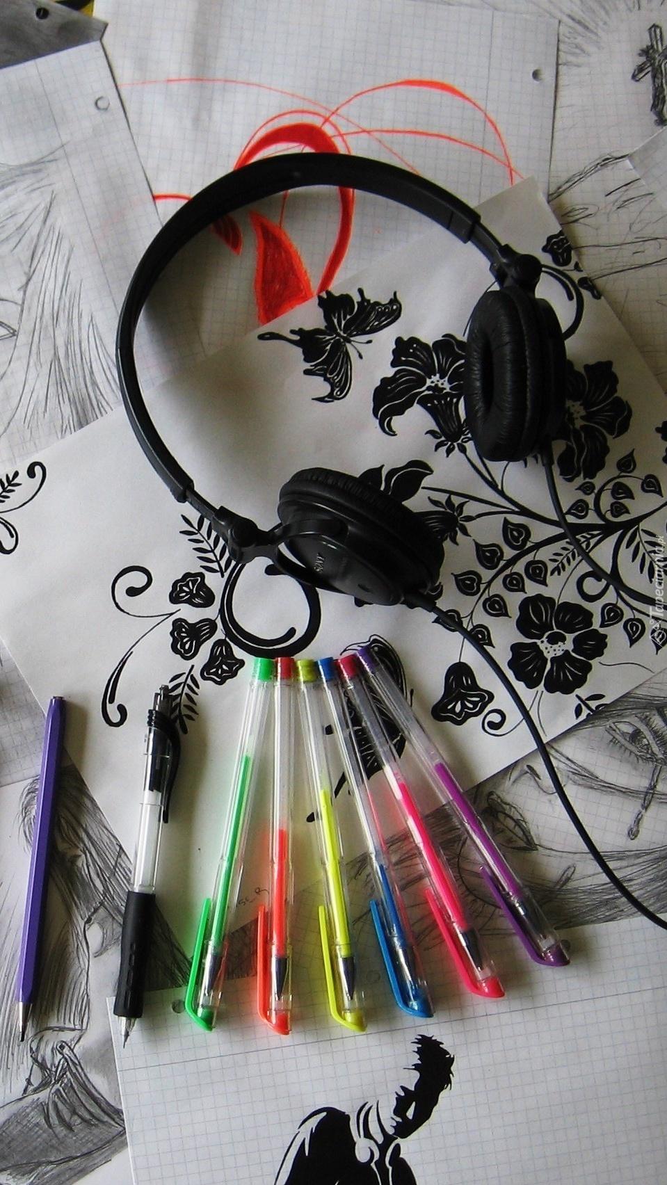 Słuchawki obok długopisów