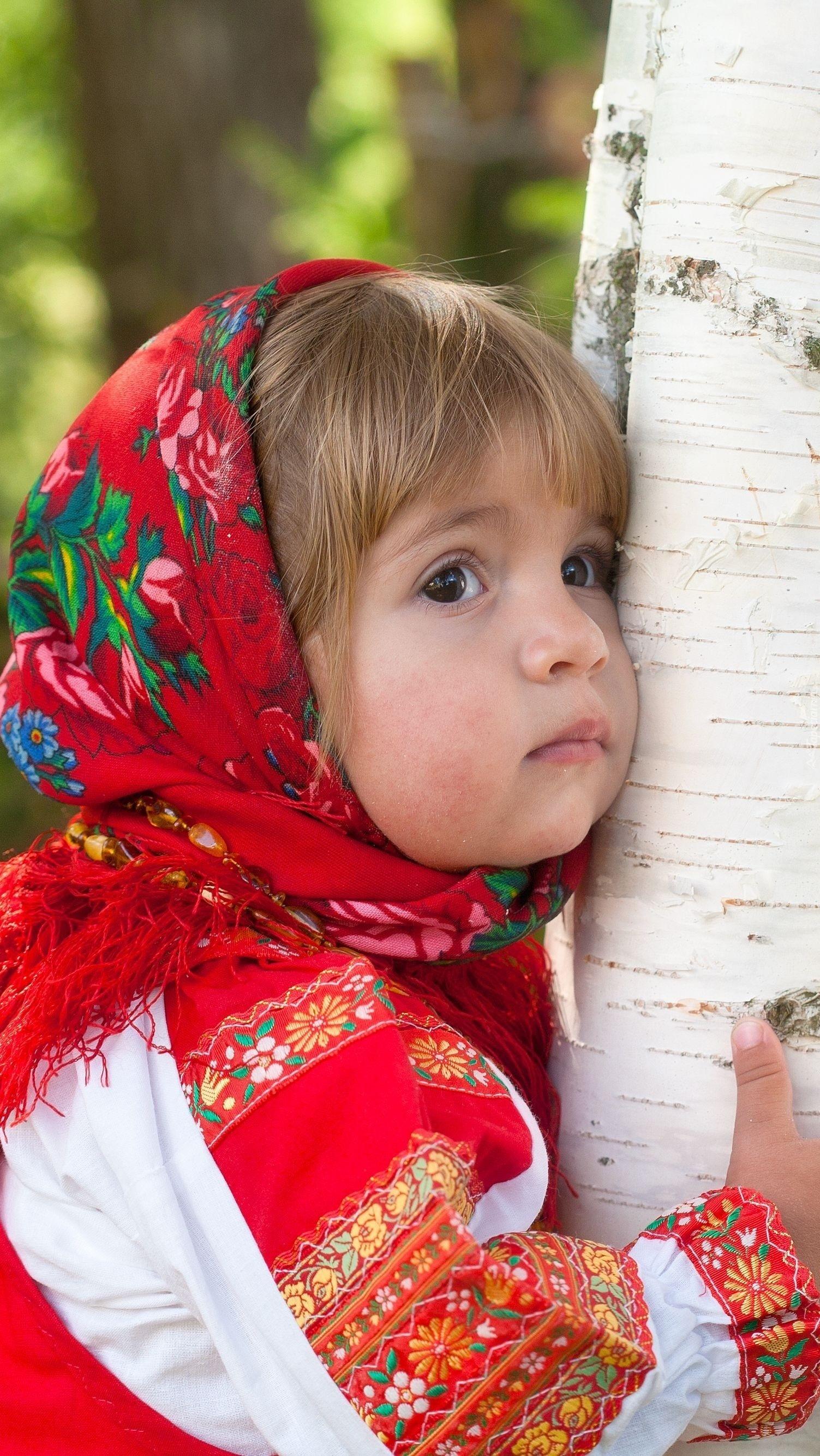 Smutna dziewczynka w chusteczce obok brzozy