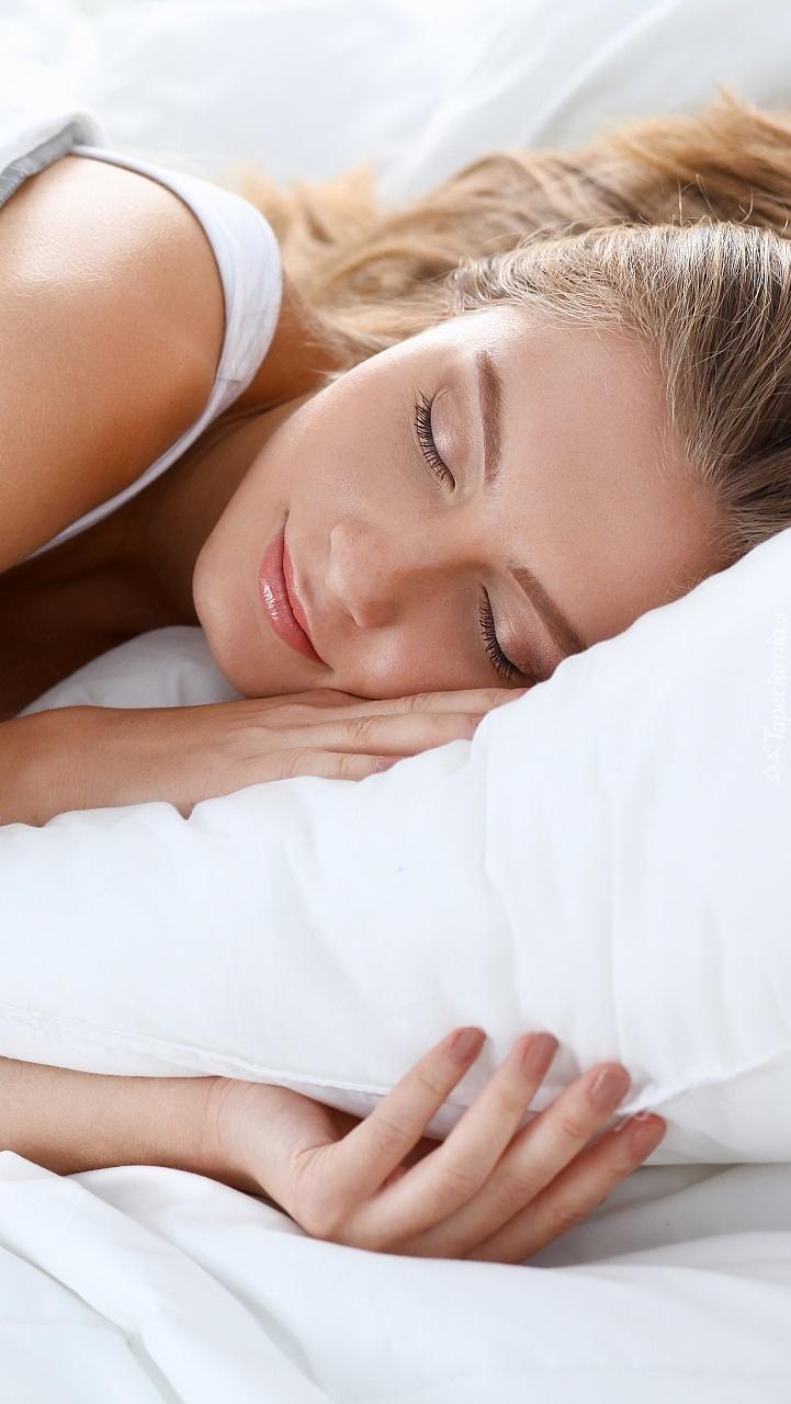 Śpiąca kobieta w białej pościeli