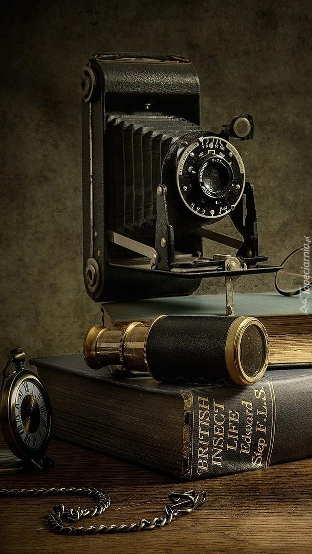 Stary aparat fotograficzny oparty na książce z lornetką i zegarkiem