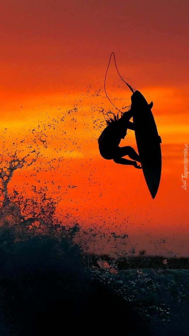 Surfer w zachodzącym słońcu