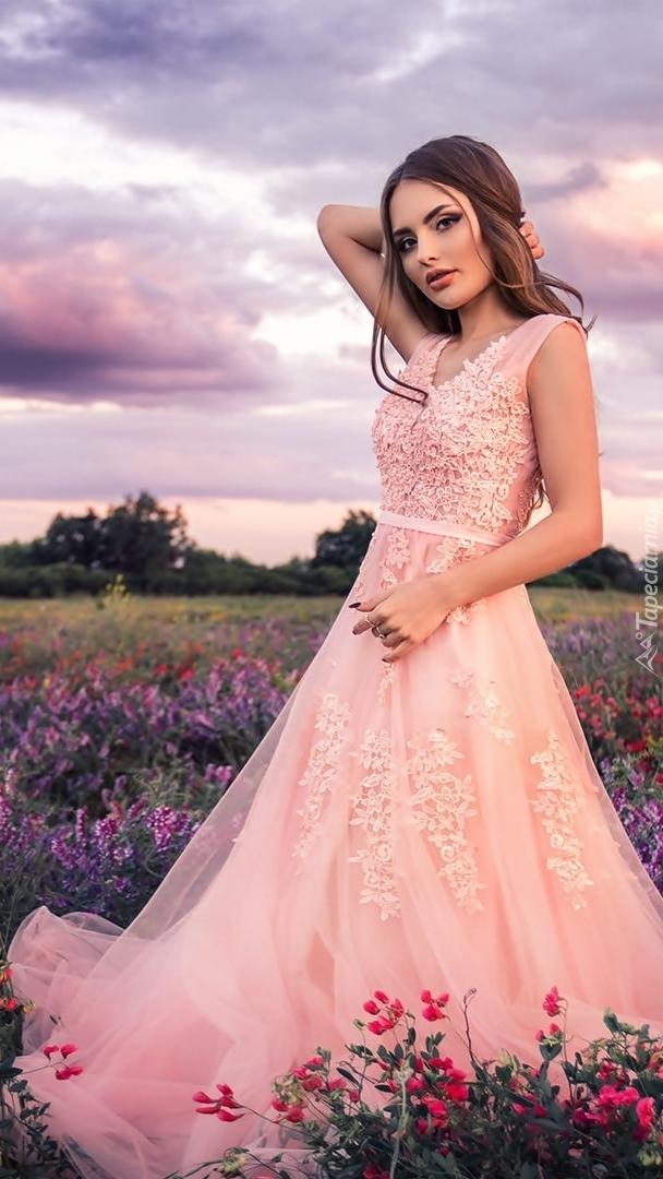 Szatynka w sukience na kwiecistej łące