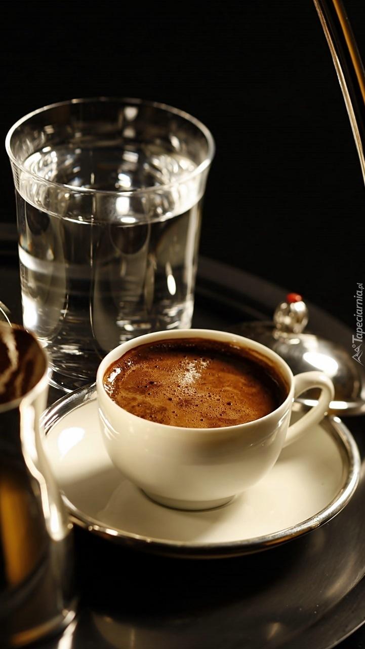 Szklanka wody obok filiżanki z kawą