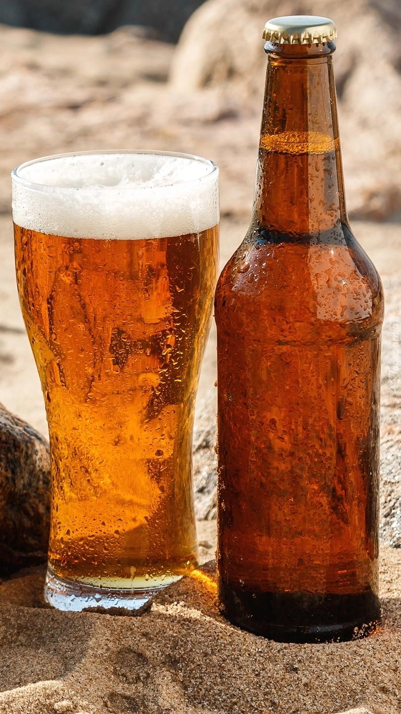 Szklanka z piwiem obok butelki na piasku