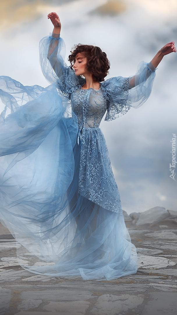 Tańcząca kobieta w niebieskiej sukni