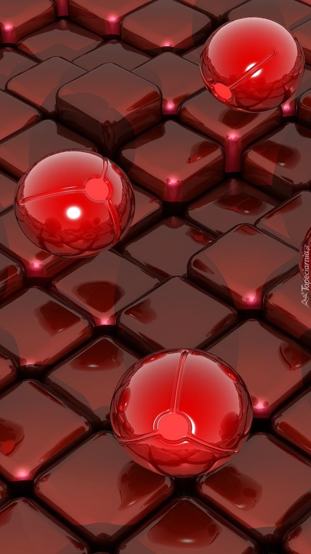 Trzy lśniące kule na kwadratowych przyciskach