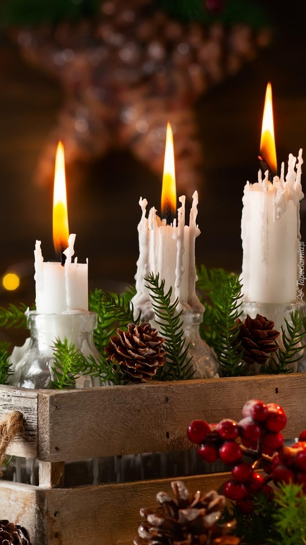 Trzy zapalone świeczki w skrzynce