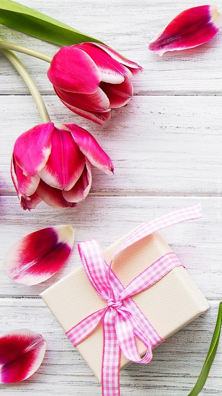 Tulipany i jego płatki obok prezentu
