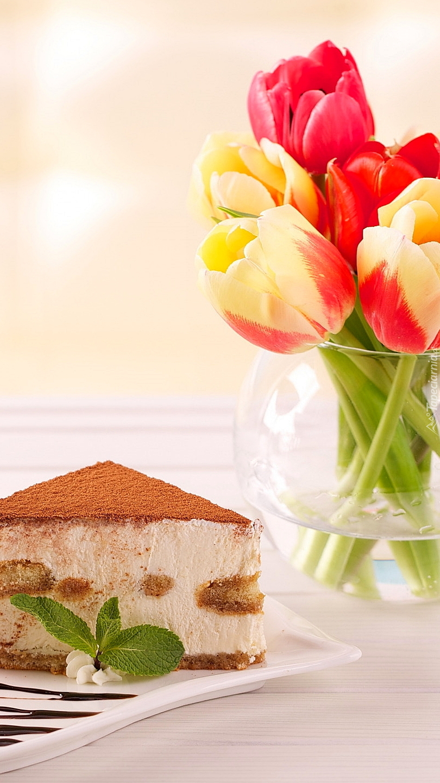 Tulipany w wazonie obok ciasta