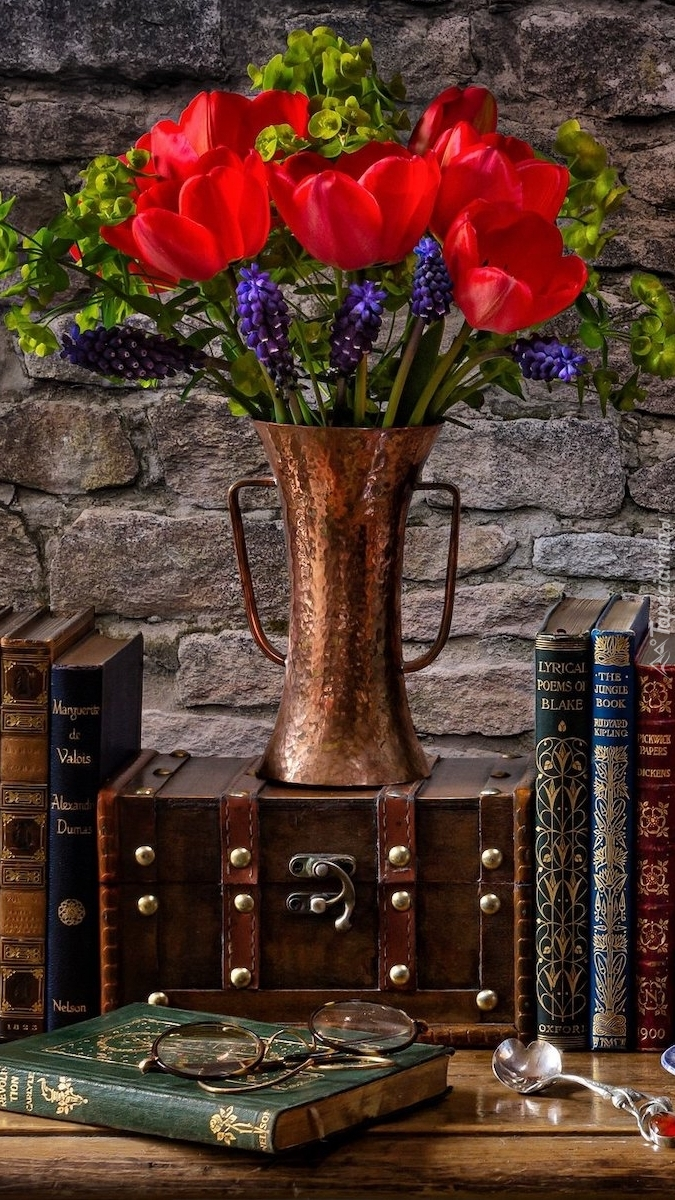 Tulipany w wazonie obok książek