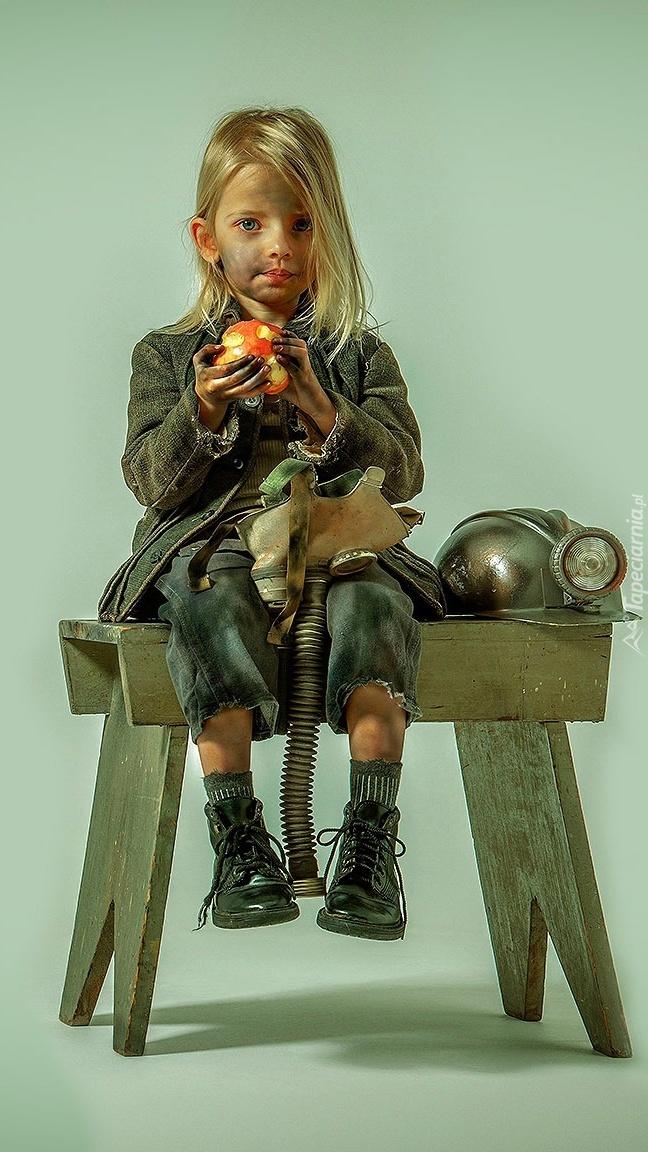 Umorusana twarz dziewczynki siedzącej na krześle z jabłkiem w dłoniach