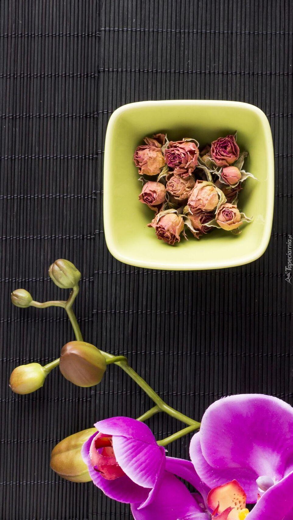 Uschnięte różyczki w miseczce obok storczyków