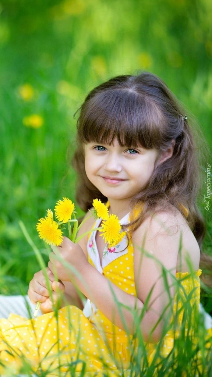 Uśmiechnięta dziewczynka z żółtymi kwiatkami na letniej łące