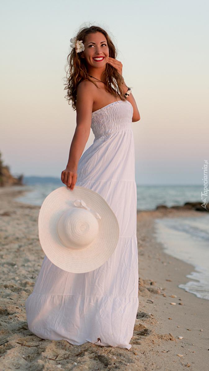 Uśmiechnięta kobieta na brzegu morza