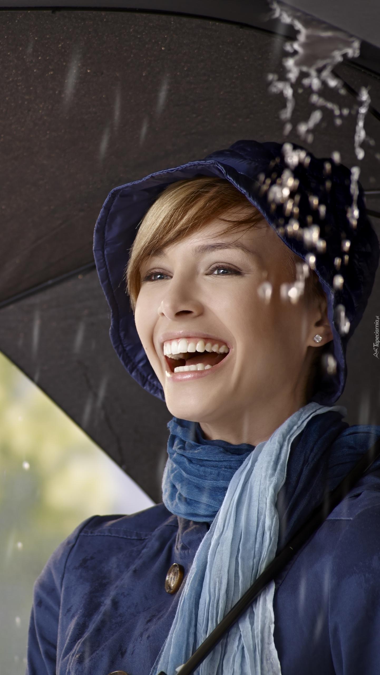 Uśmiechnięta kobieta pod parasolem