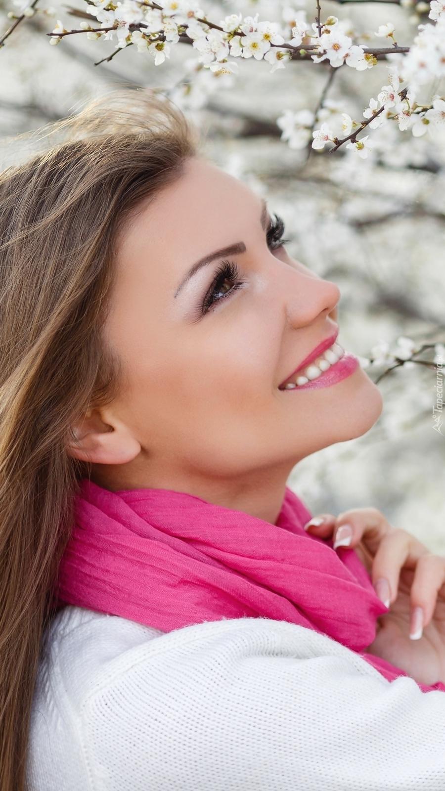 Uśmiechnięta kobieta w różowym szaliku