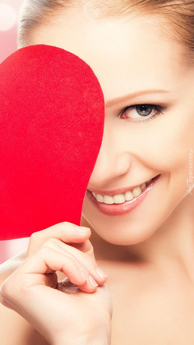Uśmiechnięta kobieta z sercem w dłoni