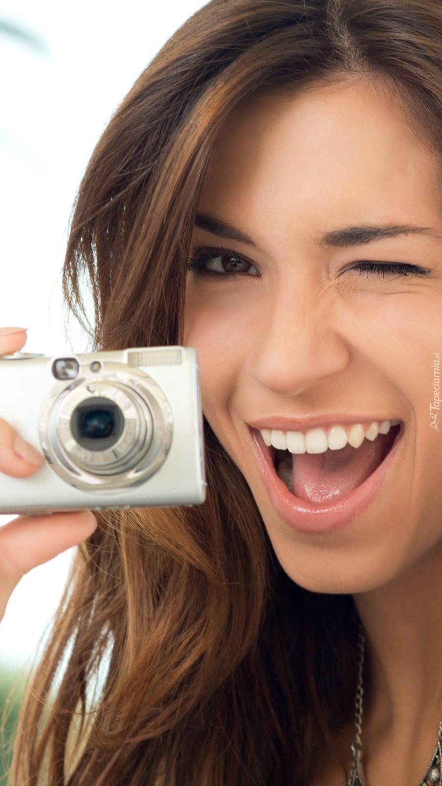 Uśmiechnięta szatynka z aparatem fotograficznym