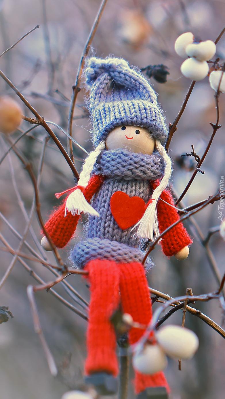 Wełniana laleczka na krzaku śnieguliczki