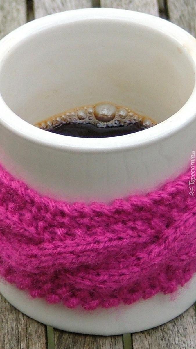 Wełniana opaska nałożona na kubek z kawą