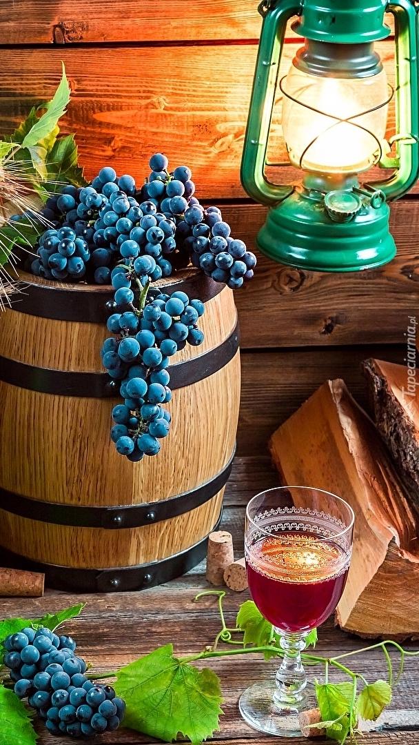 Winogrona na beczce obok lampy