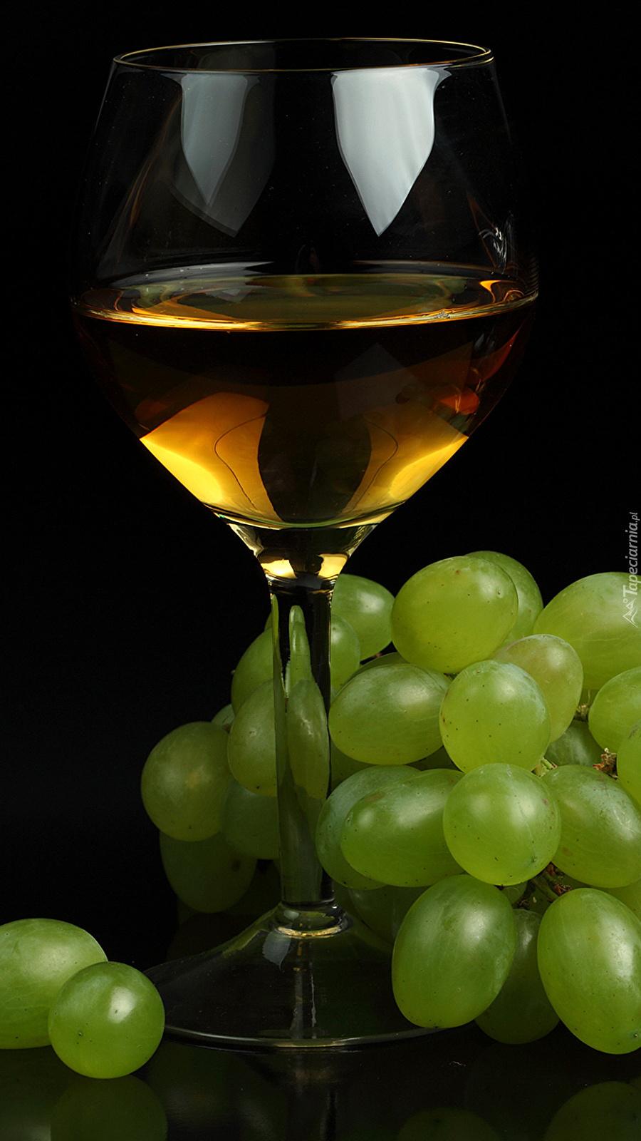 Winogrona obok kieliszka z winem