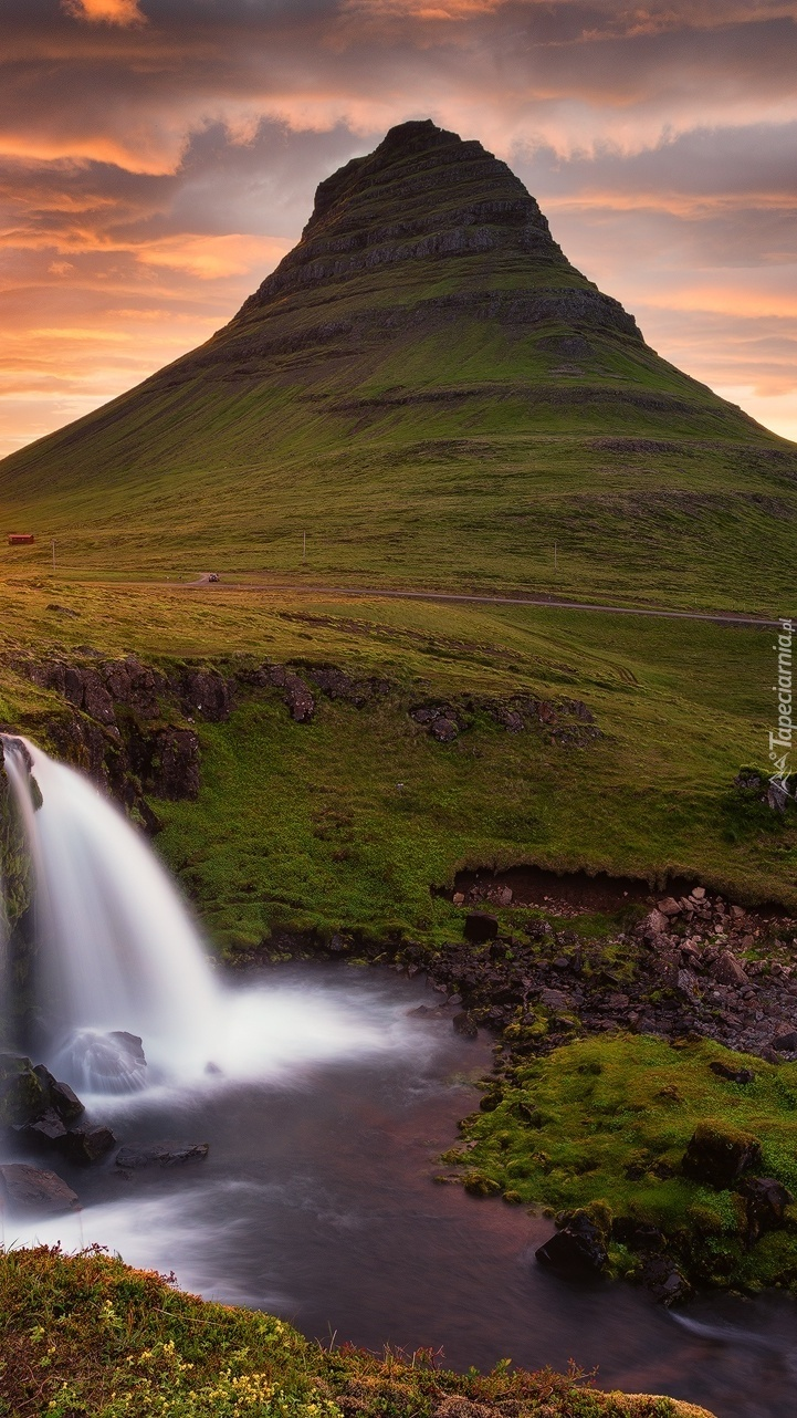 Wodospad Kirkjufellsfoss u podnóża góry Kirkjufell w promieniach słońca