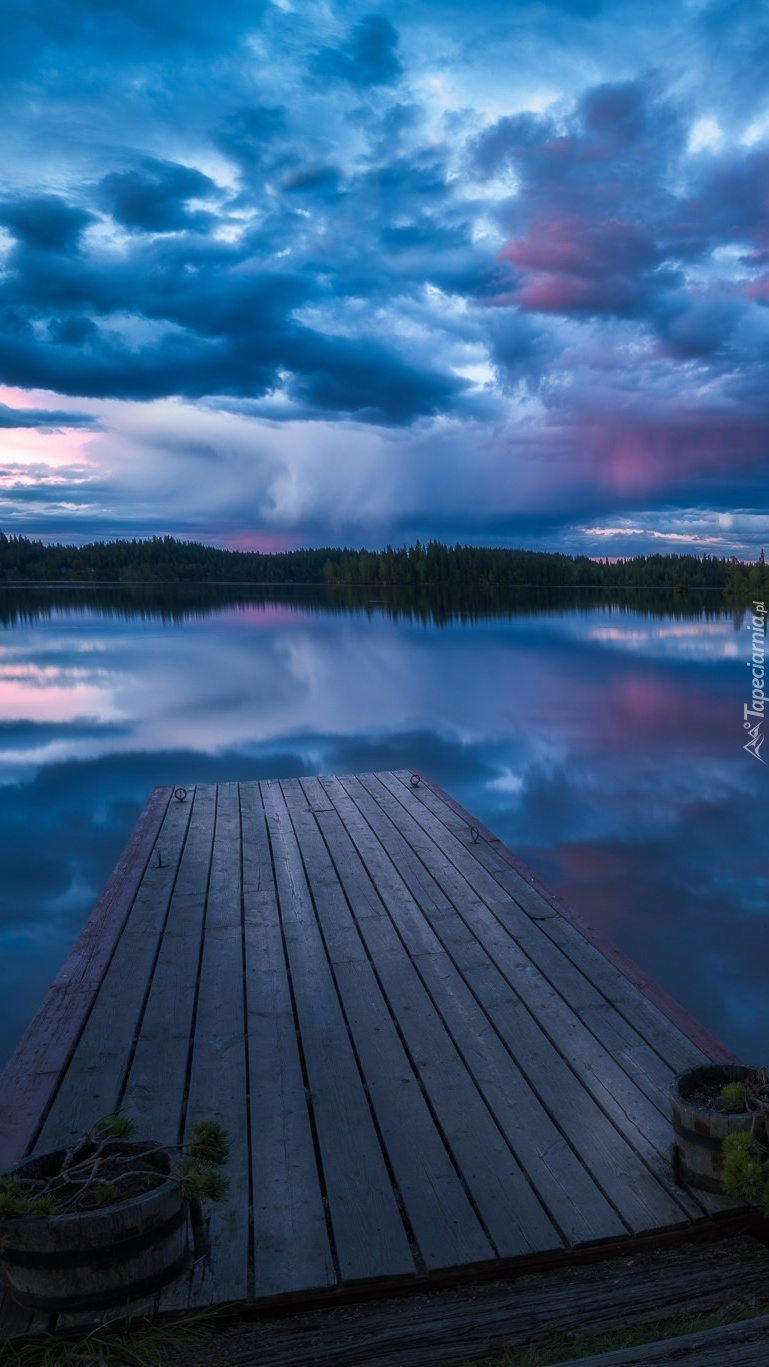 Zachmurzone niebo nad  jeziorem i pomostem